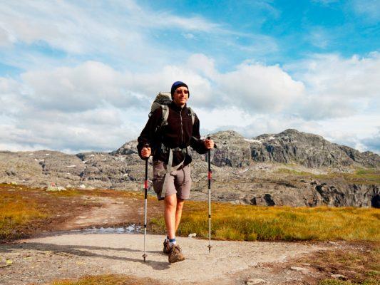 Mann går i fjellet med staver